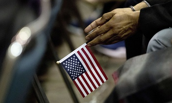 Rupinder Garha, an immigrant from India, holds a small U.S. flag during a naturalization ceremony at the Los Angeles Convention Center, Wednesday, Feb. 15, 2017, in Los Angeles.