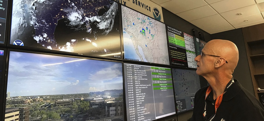 In this Wednesday, July 18, 2018 photo, National Weather Service forecaster Marvin Percha reviews monitors that track satellite and Doppler radar images, as well as his colleagues' forecasts posted on social media, at the agency's operating center in Az.