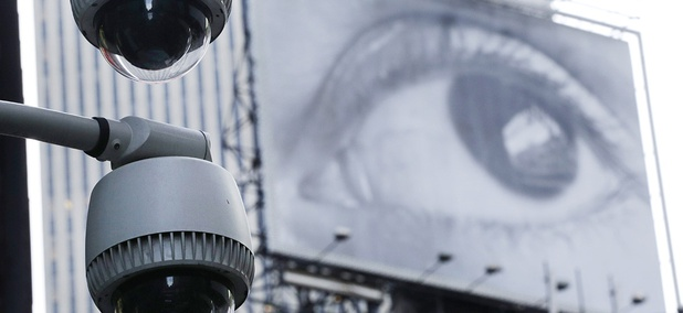 Security cameras are mounted on the side of a building overlooking an intersection in midtown Manhattan.