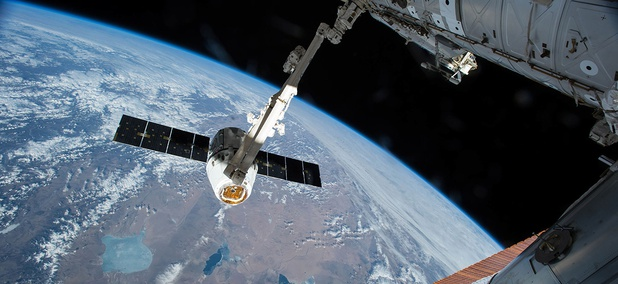 The Canadarm 2 reaches out to capture the SpaceX Dragon cargo spacecraft for docking to the International Space Station.