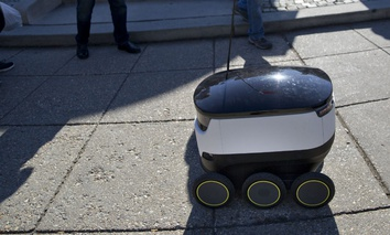 Six-wheeled ground delivery robot, from Estonia-based Starship Technologies, share the sidewalk with pedestrians at DuPont Circle, February 2017 in Washington.