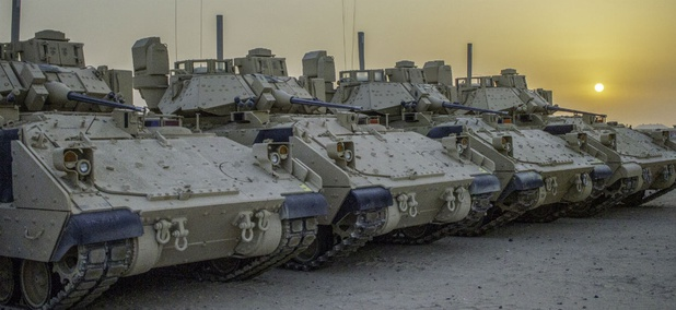 Four M2A3 Bradley Infantry Fighting Vehicles are illuminated by the rising sun in a motor pool located at Camp Buehring, Kuwait, July 19, 2018.