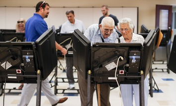 Voters cast their ballots among an array of electronic voting machines in a polling station.