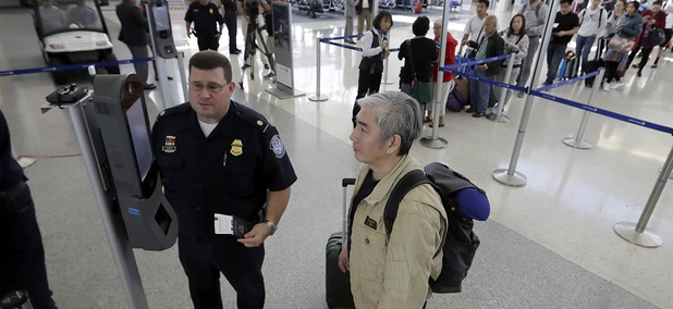 U.S. Customs and Border Protection supervisor Erik Gordon, left, helps a passenger navigate one of the new facial recognition kiosks at a United Airlines gate before boarding a flight to Tokyo.