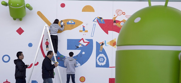 Attendees at the Google Developer Day walks past a mural being painted in Beijing, China, Thursday, Dec. 8, 2016.