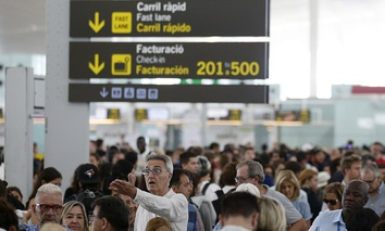Passengers wait for pass the security control at Barcelona airport in Prat Llobregat, Spain, Friday, Aug. 11, 2017.