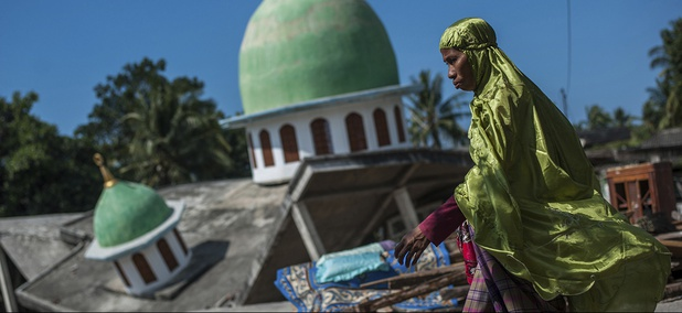 A woman walks past a mosque collapsed during Sunday's earthquake in Gangga, Lombok Island, Indonesia.
