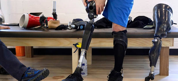 Boston Marathon bombing survivor Marc Fucarile holds his thigh socket as he tests a variety of microprocessor-controlled prosthetic knees, during a visit to the Medical Center Orthotics and Prosthetics in the Allston neighborhood of Boston.