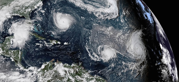 This enhanced satellite image made available by NOAA shows Tropical Storm Florence, upper left, in the Atlantic Ocean on Tuesday, Sept. 11, 2018.