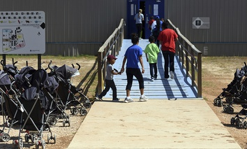 Immigrants walk into a building at South Texas Family Residential Center in Dilley, Texas.
