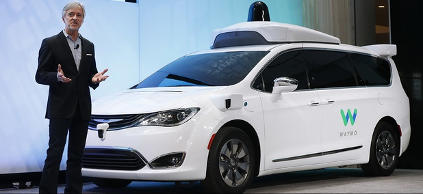 John Krafcik, CEO of Waymo, introduces a Chrysler Pacifica hybrid outfitted with Waymo's own suite of sensors and radar, at the North American International Auto Show in Detroit.
