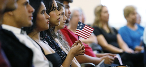New citizens hold an American flag as they listen during a naturalization ceremony at the U.S. Citizenship and Immigration Services Kendall Field Office, Thursday, Aug. 30, 2018, in Miami.