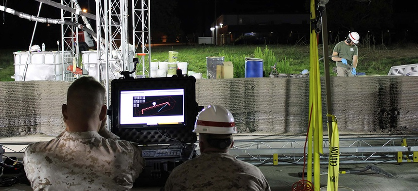Marines from I Marine Expeditionary Force monitor the computer while the world's largest concrete 3D printer constructs a 500-square-foot barracks hut at the U.S. Army Engineer Research and Development Center in Champaign, Illinois.