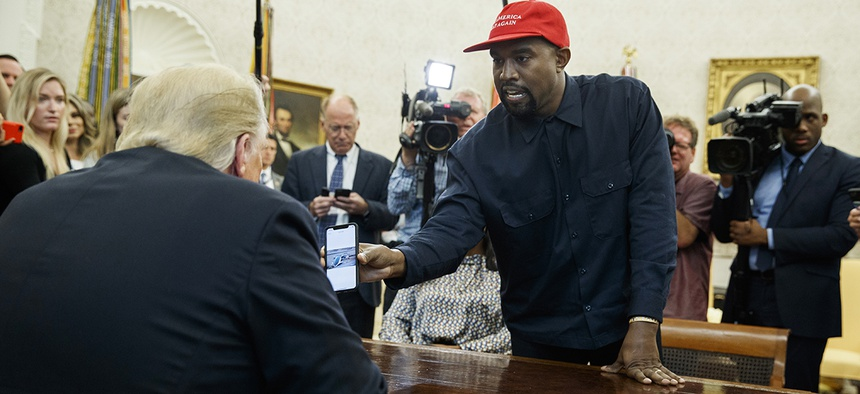Rapper Kanye West shows President Donald Trump a photograph of a hydrogen plane during a meeting in the Oval Office of the White House, Thursday, Oct. 11, 2018, in Washington.