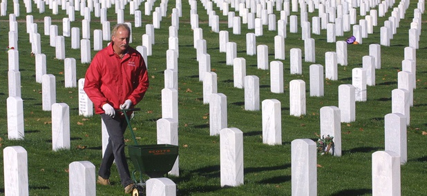 Tim Descit, an Army veteran, spreads fertilizer on the grounds of the National Cemetery at the Dayton, Ohio Veterans Administration grounds.