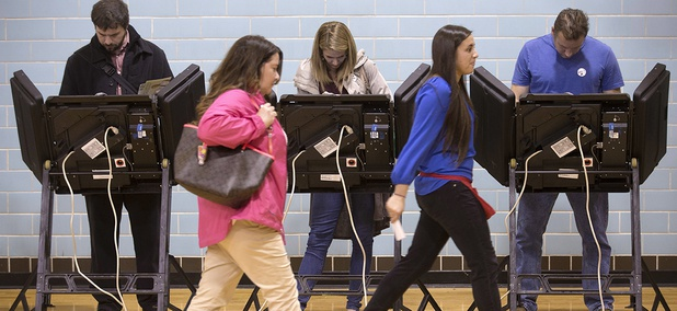 A poll worker leads a voter to an electronic voting machine at the Schiller Recreation Center polling station on election day in Columbus, Ohio.