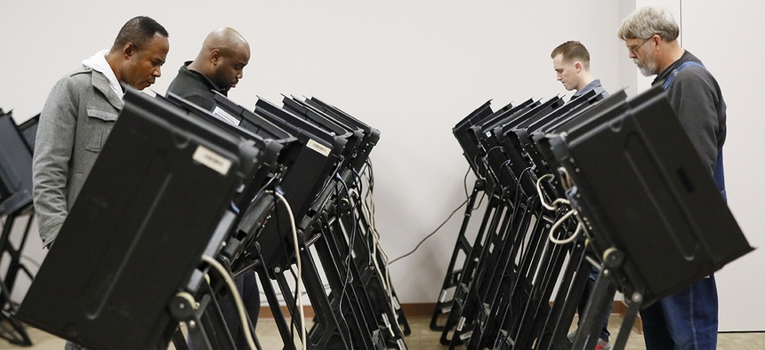 Voters use electronic polling machines as they cast their votes early at the Franklin County Board of Elections, Wednesday, Oct. 31, 2018, in Columbus, Ohio.