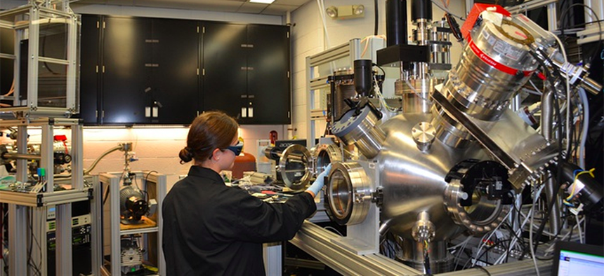 Ashley Wissel, Purdue University undergraduate student, works with the pulsed laser deposition chamber in the Materials and Manufacturing Directorate. This is used to study growth of thin layers of material at low temperatures.