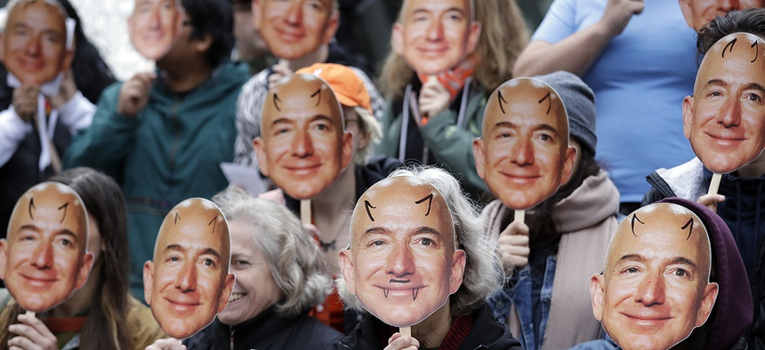 Demonstrators hold images of Amazon CEO Jeff Bezos near their faces during a Halloween-themed protest at Amazon headquarters over the company's facial recognition system.