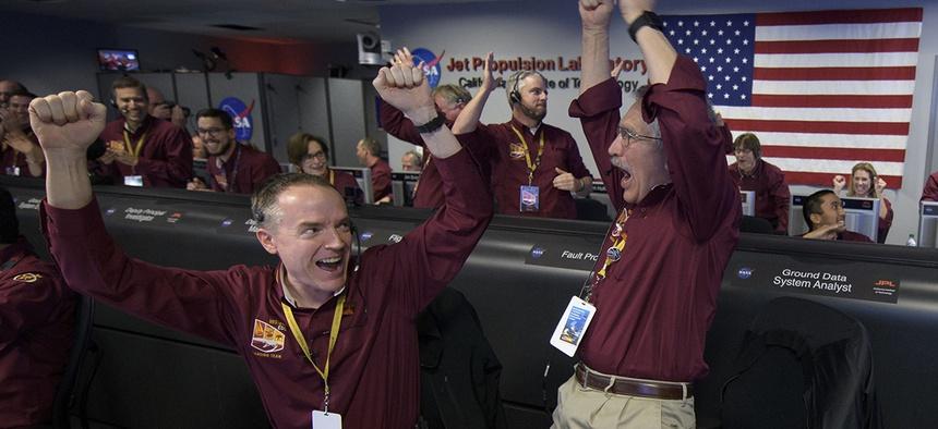 Mars InSight team members Kris Bruvold, left, and Sandy Krasner rejoice, Monday, Nov. 26, 2018, inside the Mission Support Area at NASA's Jet Propulsion Laboratory in Pasadena, Calif.