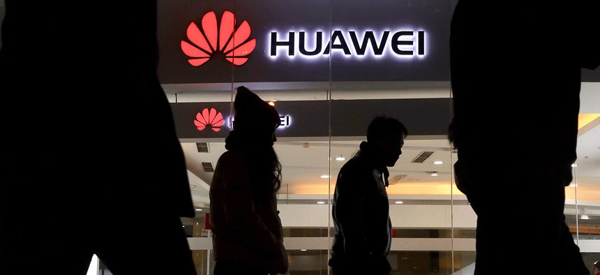 Pedestrians walk past a Huawei retail shop in Beijing Thursday, Dec. 6, 2018.