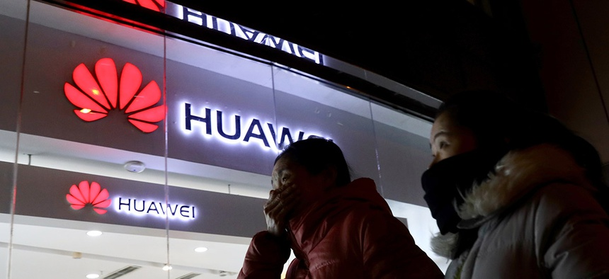 Women walk past a Huawei retail shop in Beijing Thursday, Dec. 6, 2018.