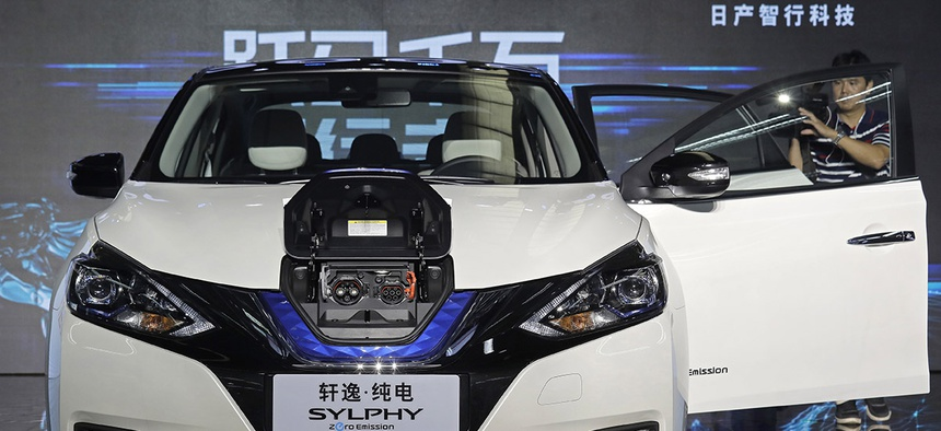 A cameraman takes video of a Nissan Sylphy Zero Emission, the Nissan's first all-electric vehicle built in China, at the Nissan factory in Guangzhou, Guangdong province, China.