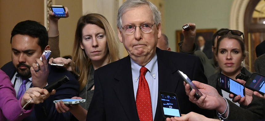 Senate Majority Leader Mitch McConnell of Ky., center, talks with reporters as he walks on Capitol Hill in Washington, Wednesday, Jan. 2, 2019, after returning from a meeting with President Donald Trump at the White House.
