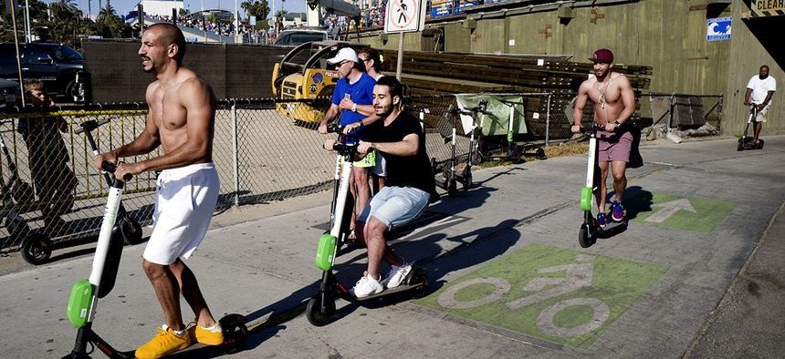 People ride Lime and Bird scooters along the strand in Santa Monica, Calif.