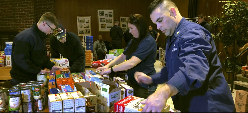 Members of the Coast Guard stock a pantry that was created  to help hundreds of civilian and non-civilian employees to help makes ends meet during the partial federal government shutdown.