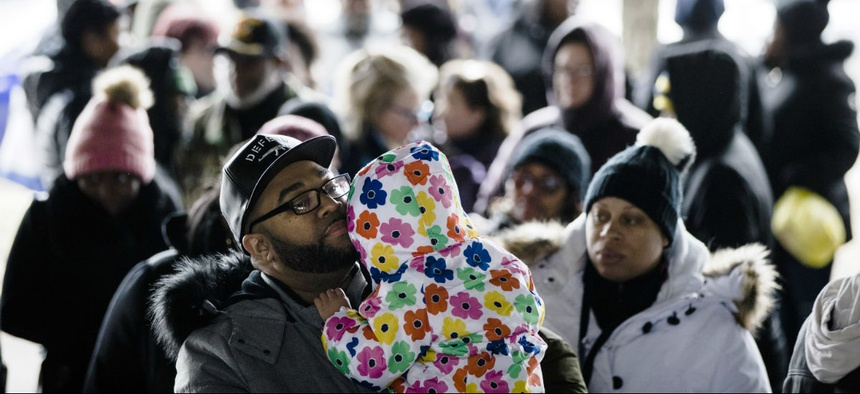 A furloughed federal worker holds his daughter as they wait in line with others who are affected by the partial government shutdown for Philabundance volunteers to distribute food under Interstate 95 in Philadelphia Jan. 23.