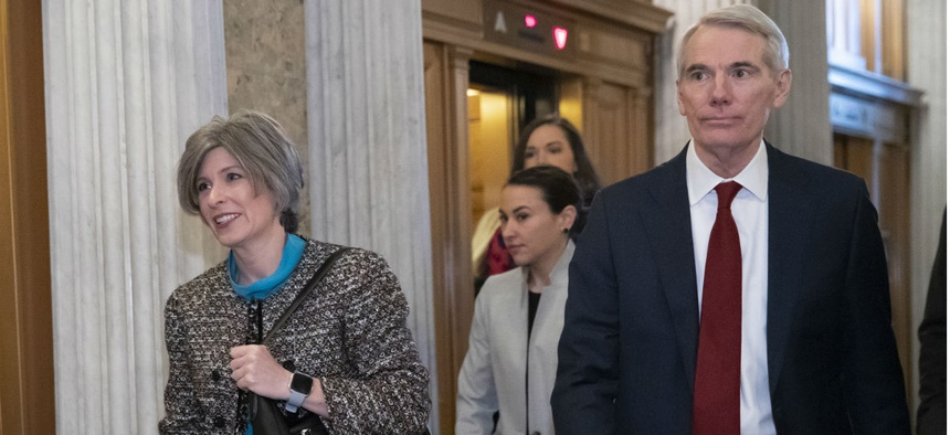 Sens. Joni Ernst, left, and Rob Portman head to the Senate floor prior to a vote on ending the partial government shutdown Jan. 24.