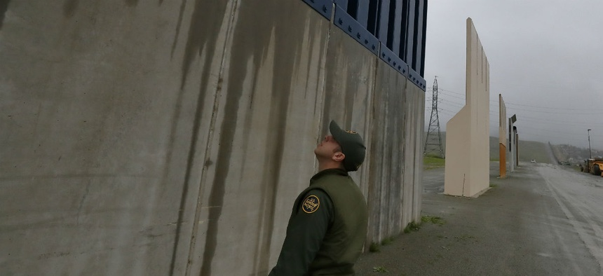 A Border Patrol agent walks towards prototypes for a border wall Feb. 5 in San Diego.