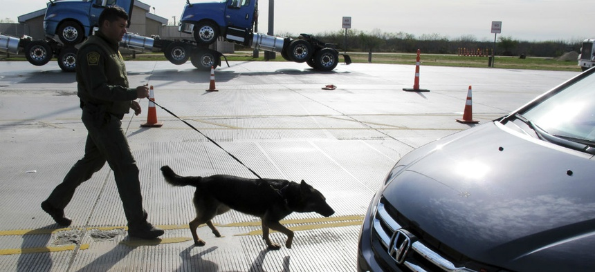 A Border Patrol agent uses a dog to inspect vehicles lining up at the Laredo North vehicle checkpoint in Laredo, Texas, Feb. 2.