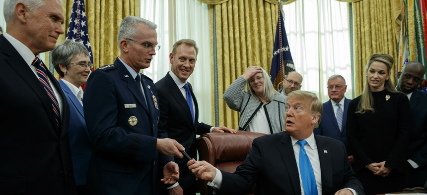 """President Donald Trump hands a pen to Air Force Gen. Paul Selva after signing """"Space Policy Directive 4"""" in the Oval Office of the White House Feb. 19."""