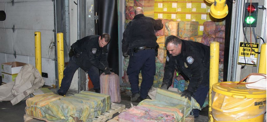 Customs agents unloading a truck containing 3,200 pounds of cocaine in 60 packages, where it was seized at the Port of New York/Newark, in Newark, N.J.