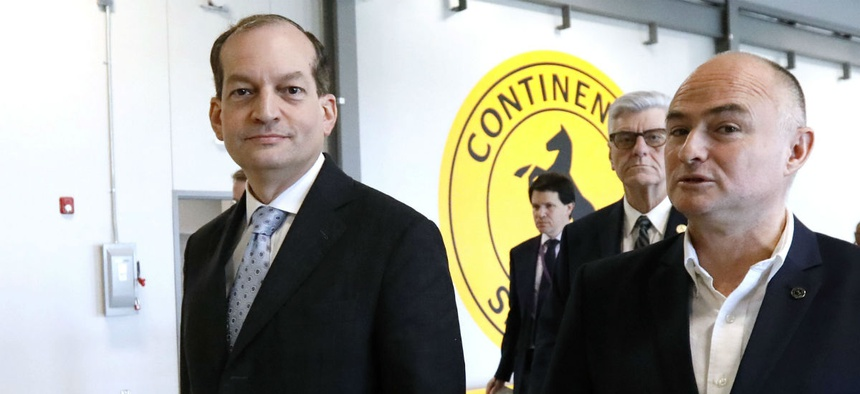 Labor Secretary Alexander Acosta, left, tours the Continental Tire Training Center Feb. 8.