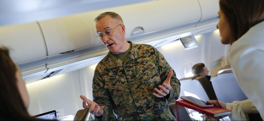 Joint Chiefs Chairman Gen. Joseph Dunford gestures while speaking to reporters during a briefing on a military aircraft before arrival at El Paso International airport in February.