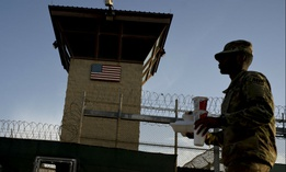 A task force member walks past the Camp VI detention facility at the Guantanamo Bay U.S. Naval Base, Cuba in 2018.