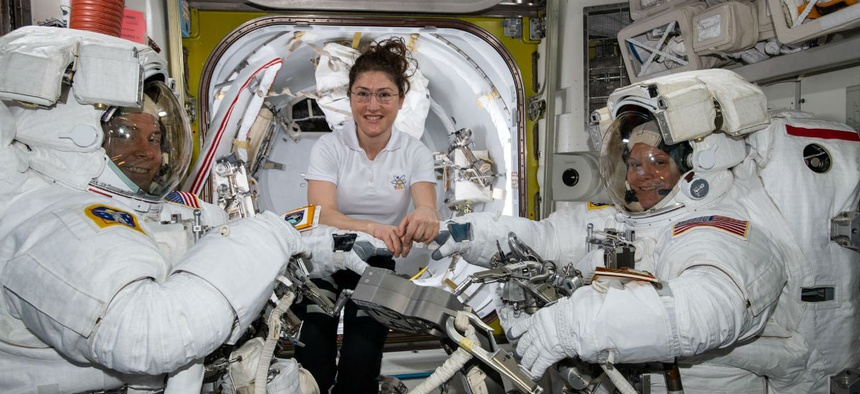 NASA astronaut Christina Koch (center) assists fellow astronauts Nick Hague (left) and Anne McClain in their U.S. spacesuits shortly before they begin the first spacewalk of their careers.
