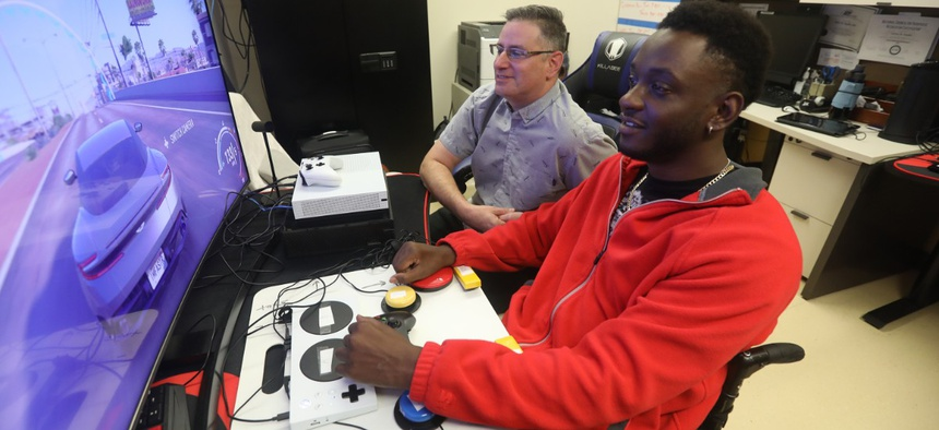Mike Monthervil, U.S. Army veteran (front), and Jamie Kaplan, recreation therapist at James A. Haley Veterans' Hospital in Tampa, Fla., play a video game using an Xbox Adaptive Controller.