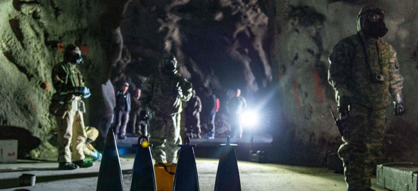 Scientists watch soldiers sample simulated leaking chemical weapons in an underground facility in order to get a better idea of both the bulky protective gear soldiers must wear as well as the dark, constrained environments they sometimes work in.