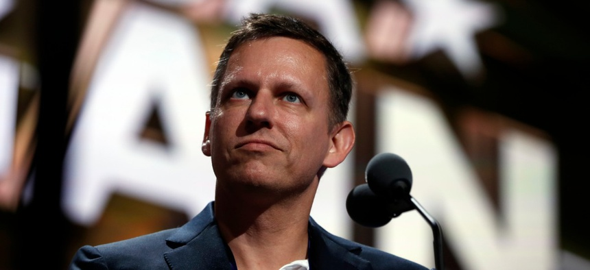 Billionaire tech investor Peter Thiel look overr the podium before the start of the second day session of the Republican National Convention in Cleveland in 2016.