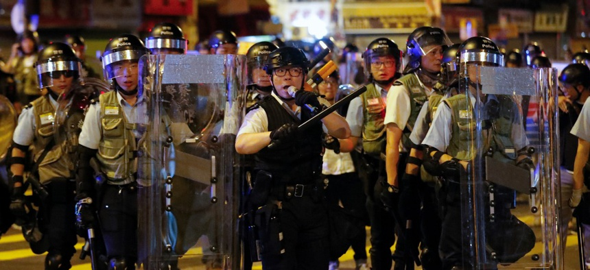 A policeman uses a speakerphone to ask residents and protesters to disperse during a protest at Sham Shui Po district in Hong Kong, Aug. 7.