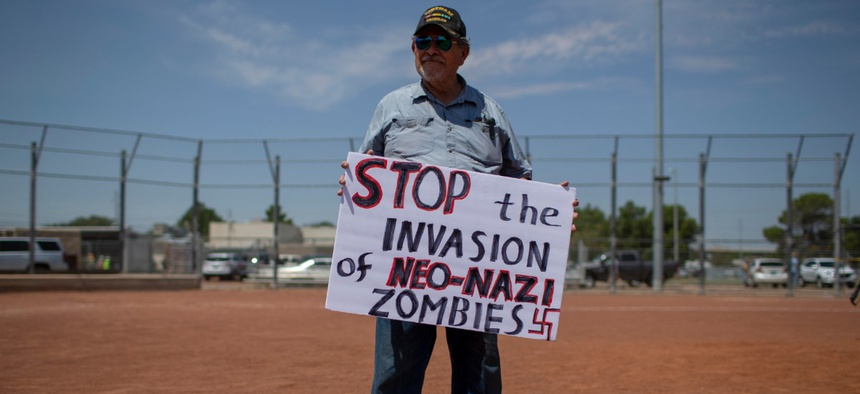 A man holds a sign to protest the visit of President Donald Trump to the border city after the Aug. 3 mass shooting in El Paso, Texas, Aug. 7.