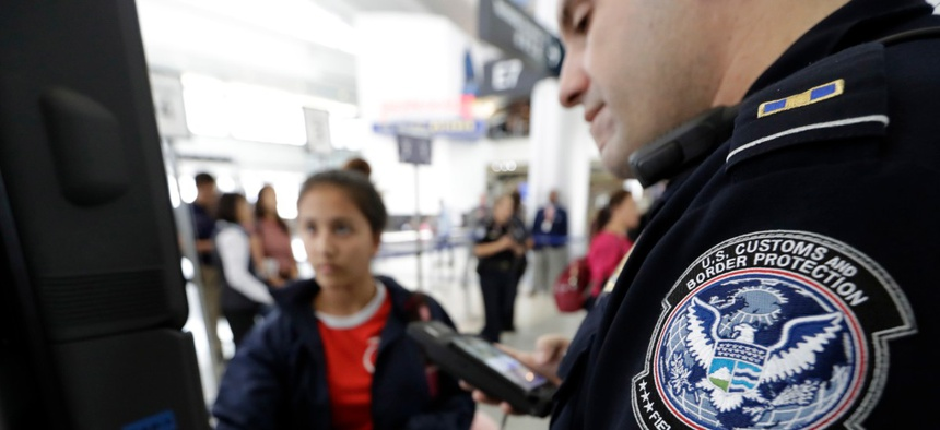 A Customs and Border Protection officer helps a passenger navigate a facial recognition kiosks at George Bush Intercontinental Airport in Houston in 2017.