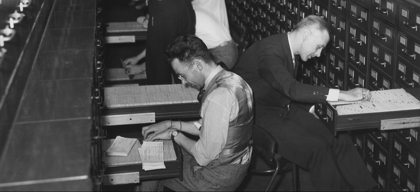 Archival photo of government employees file citizens applications for Social Security numbers, circa 1937.