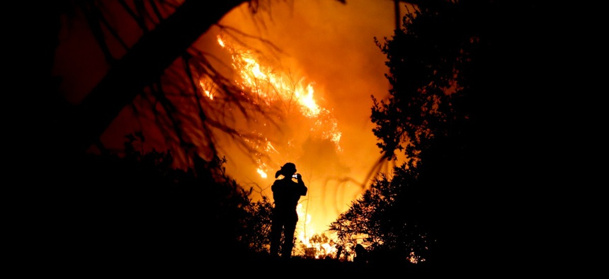 A firefighter takes a cell phone picture during a wildfire Saturday, Dec. 16, 2017, in Montecito, Calif.