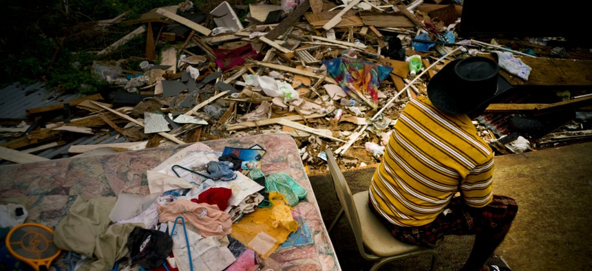 Efrain Diaz Figueroa spends the afternoon sitting on a chair next to the remains of the house of his sister destroyed by Hurricane Maria in San Juan, Puerto Rico, Monday, Oct. 9, 2017.