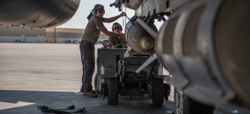 380th Expeditionary Aircraft Maintenance Squadron F-15E Strike Eagle weapons load crew members attach a munition to a F-15E at Al Dhafra Air Base, United Arab Emirates.